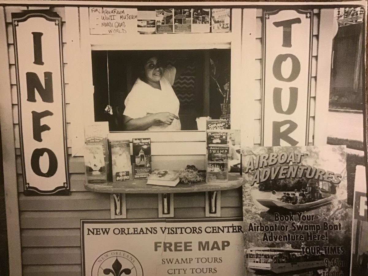 "A sepia toned photograph featuring a woman inside a tour operators stand and signs with ""info"" and ""tour"" on either side of her."